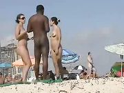 Nudist white women with nudist black man at the beach
